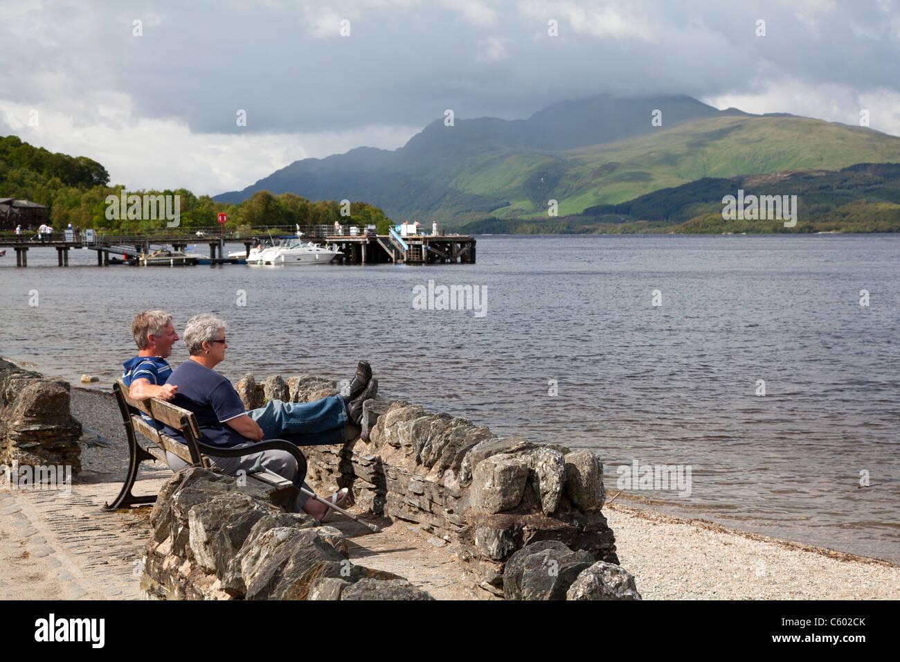 Couple enjoying the view across Loch Lomond, Luss, Argyll & Bute - Stock Image