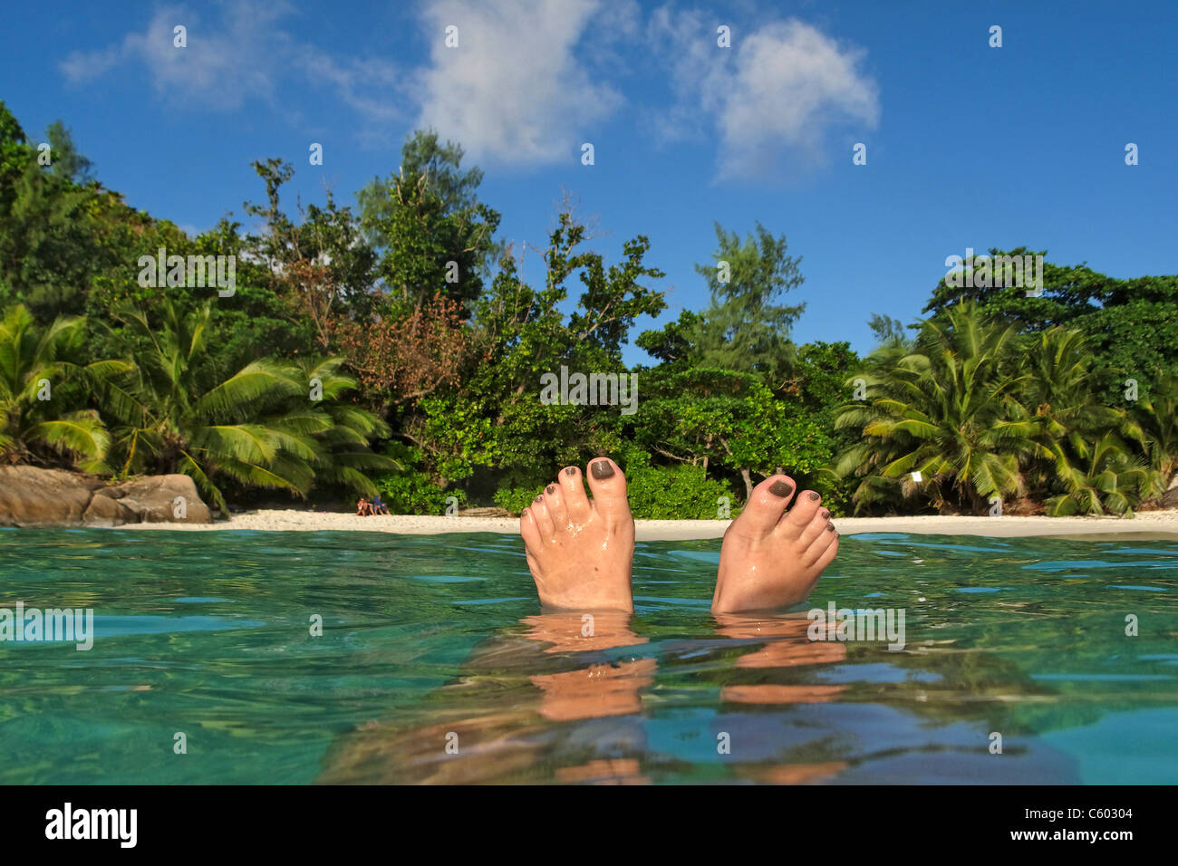 Womens Feet , Spit Level, Anse Lazio, Baie Sainte Anne district, Island of Praslin, Seychelles, Indian Ocean, Africa - Stock Image