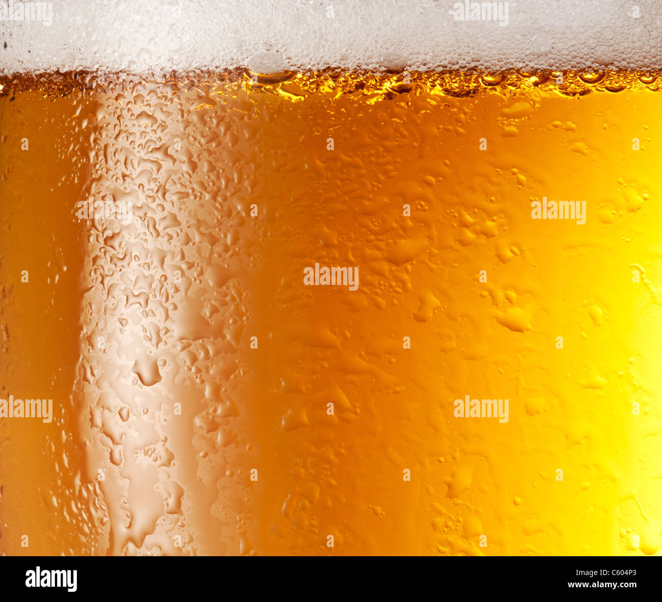 Drop and foam of beer as background. - Stock Image