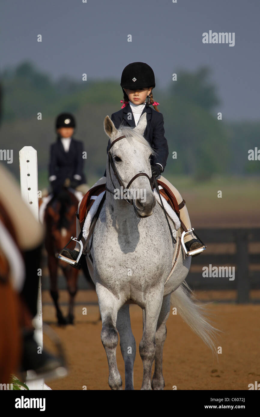 A young rider and her horse competing on the flat in a horse show. - Stock Image