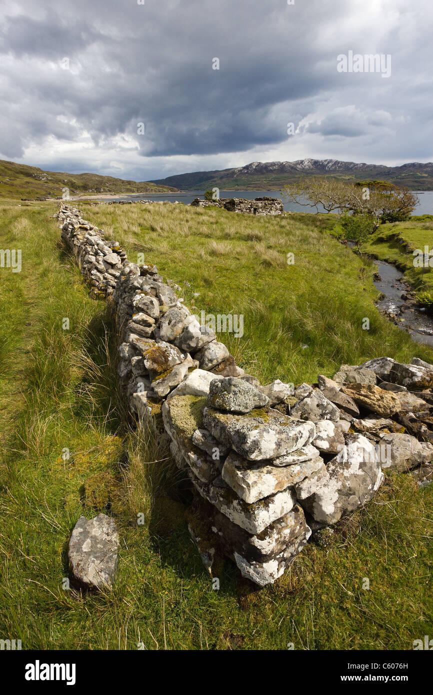 Ruined croft walls and crofts with Loch Eishort and Sleat Peninsula beyond. Boreraig, Isle of Skye, Scotland, UK - Stock Image