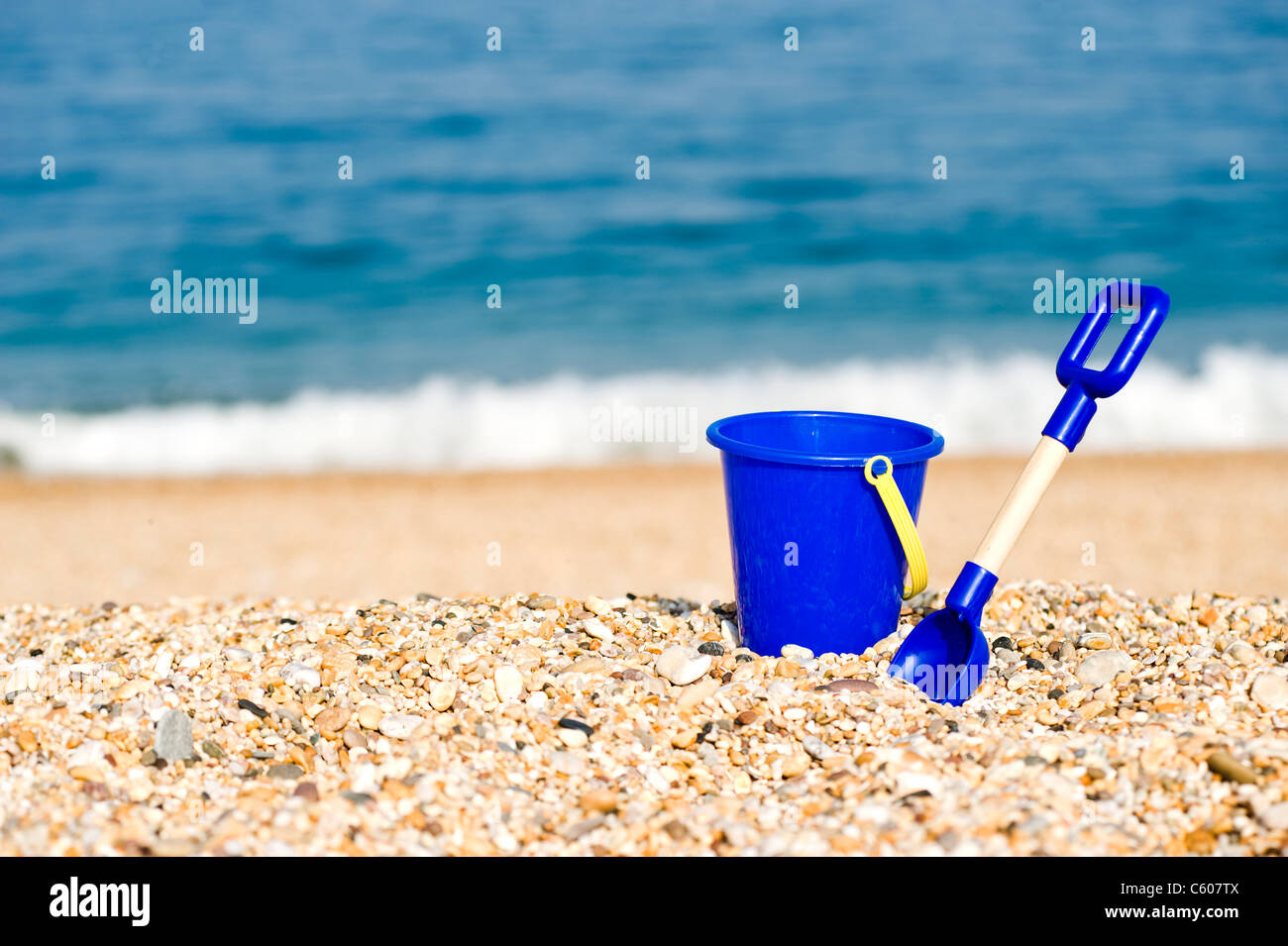 Blue Childrens Toy Bucket and Spade on the Beach - Stock Image
