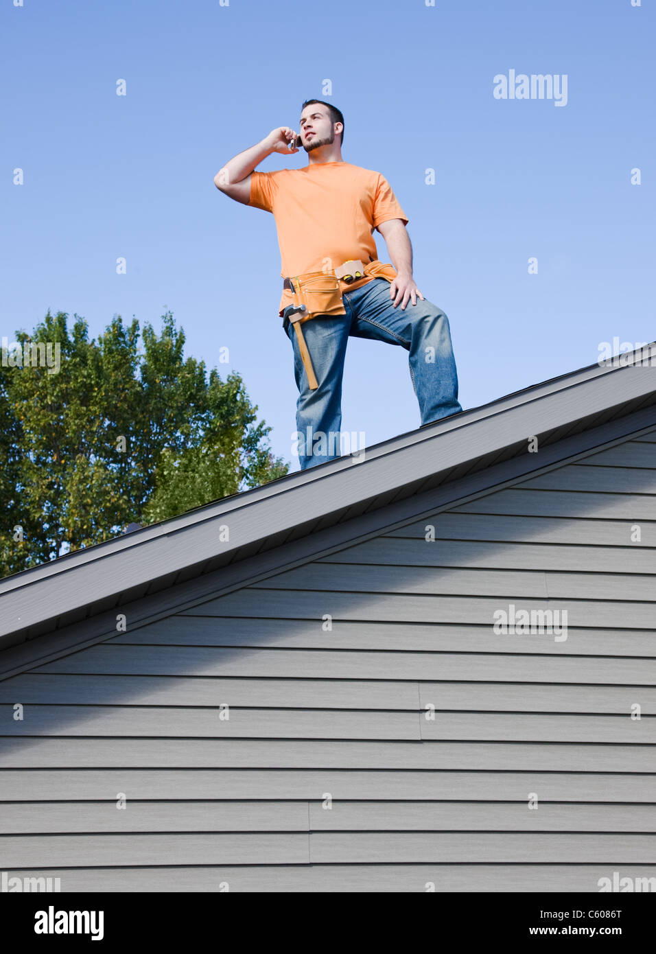 USA, Illinois, Metamora, Young worker standing on roof and talking via mobile phone - Stock Image