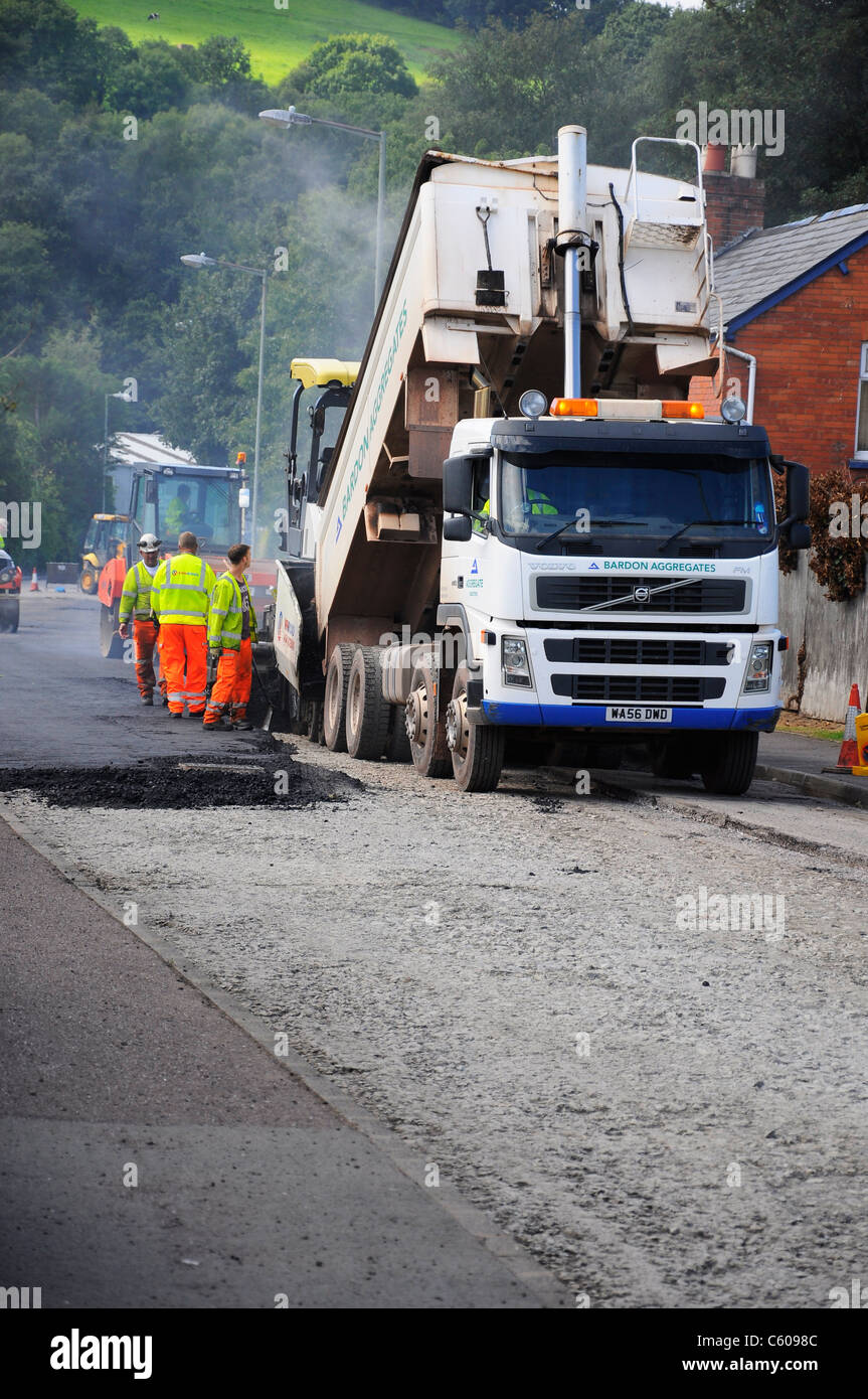 Highways maintenance workers resurfacing a local road. - Stock Image