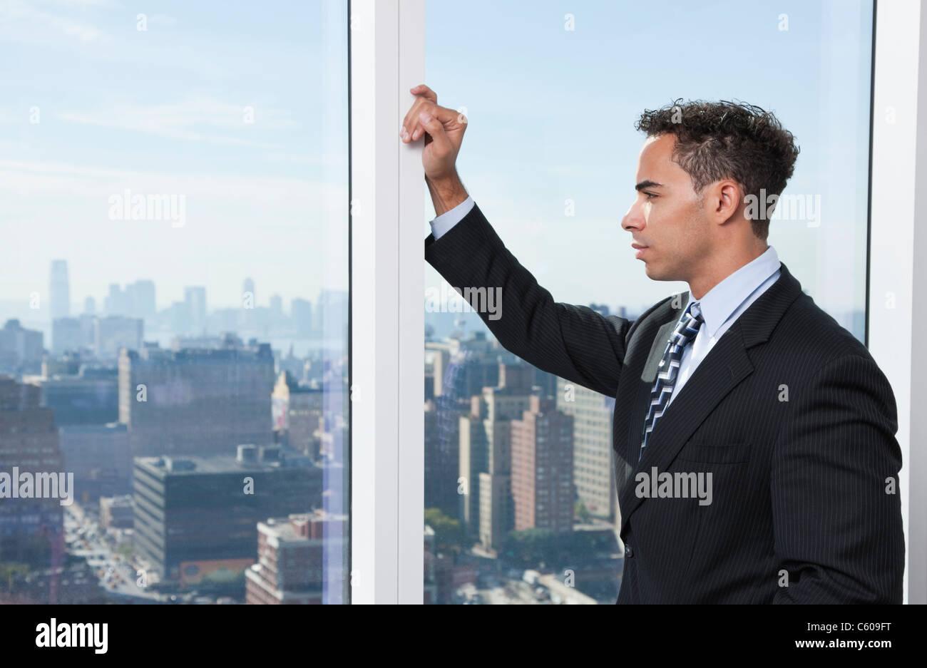 USA, New York State, New York City, business man looking through window - Stock Image