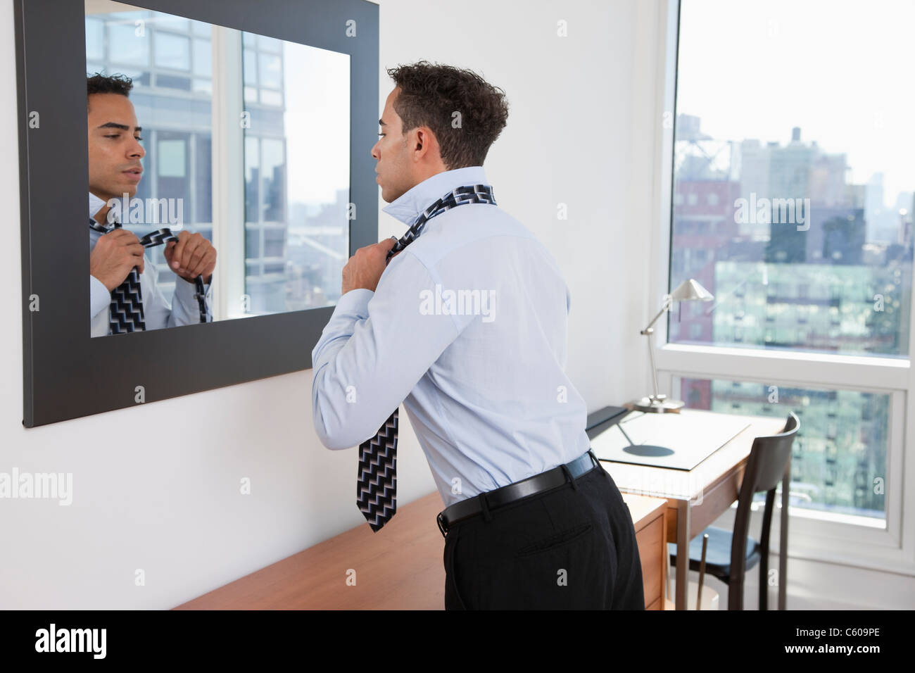 USA, New York, New York City, young man tying tie in front of mirror in hotel room - Stock Image