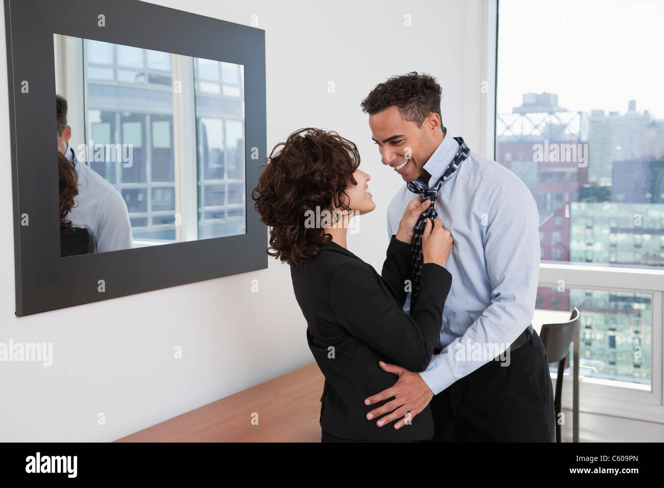 USA, New York, New York City, young woman helping smiling man tying tie in hotel room - Stock Image