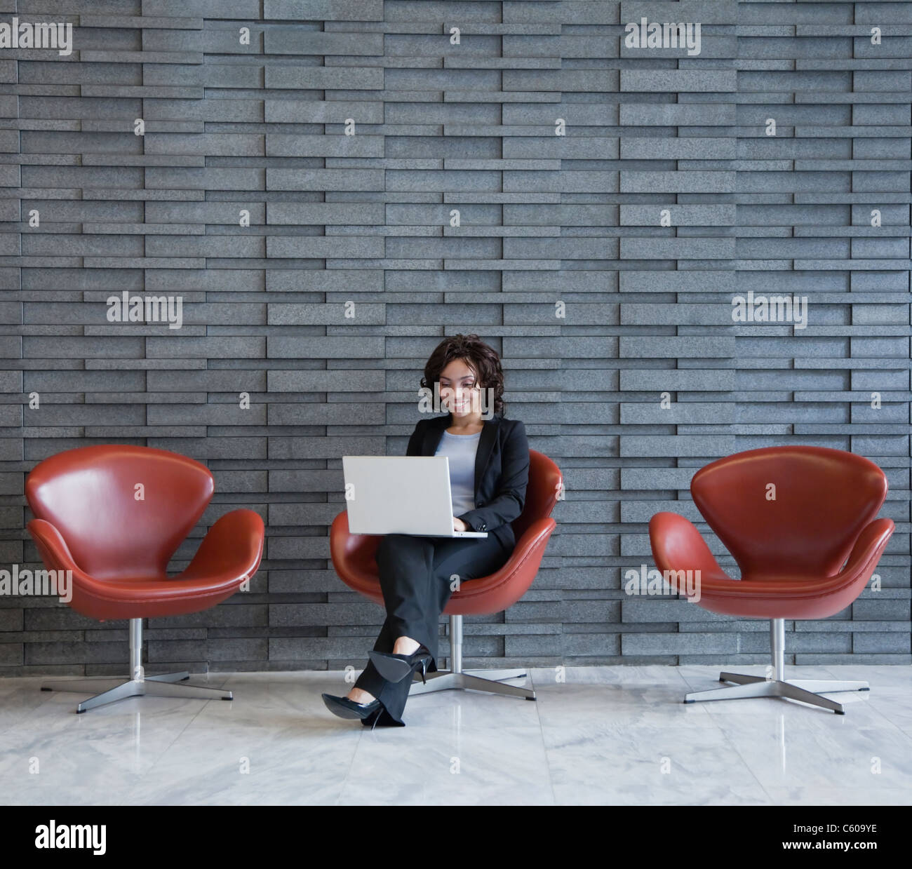 USA, New York, New York City, smiling young woman using laptop in hotel lobby - Stock Image