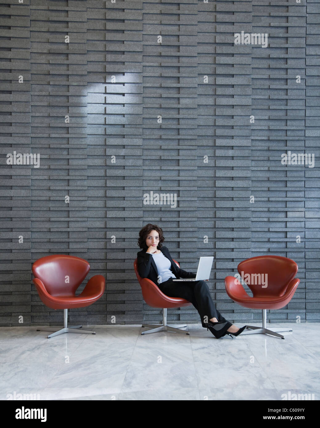 USA, New York, New York City, portrait of smiling young woman using laptop in hotel lobby - Stock Image
