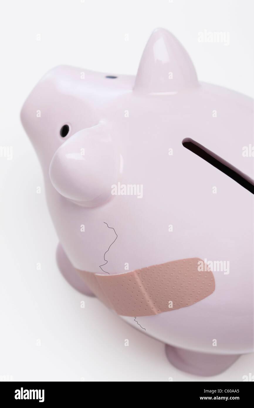 USA, Illinois, Metamora, Piggy bank with crack and bandage - Stock Image