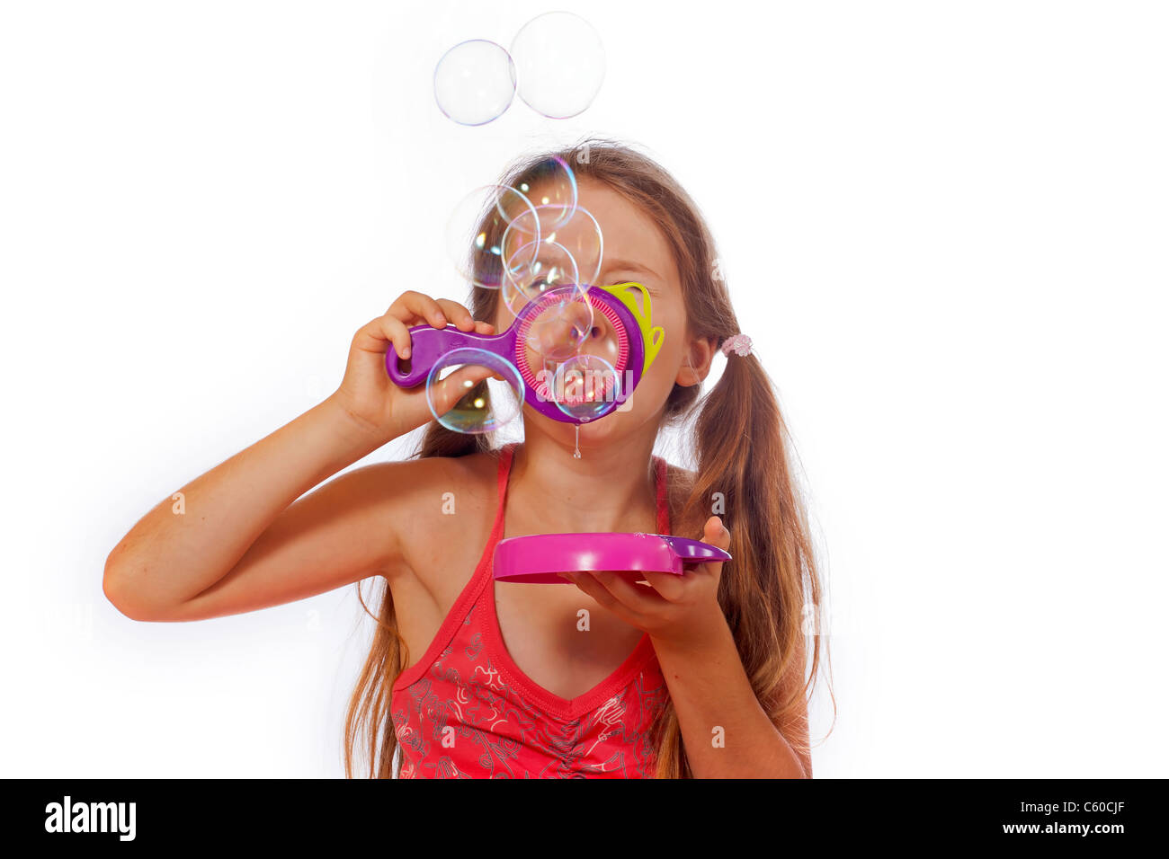eight year old girl playing with soap bubbles - Stock Image
