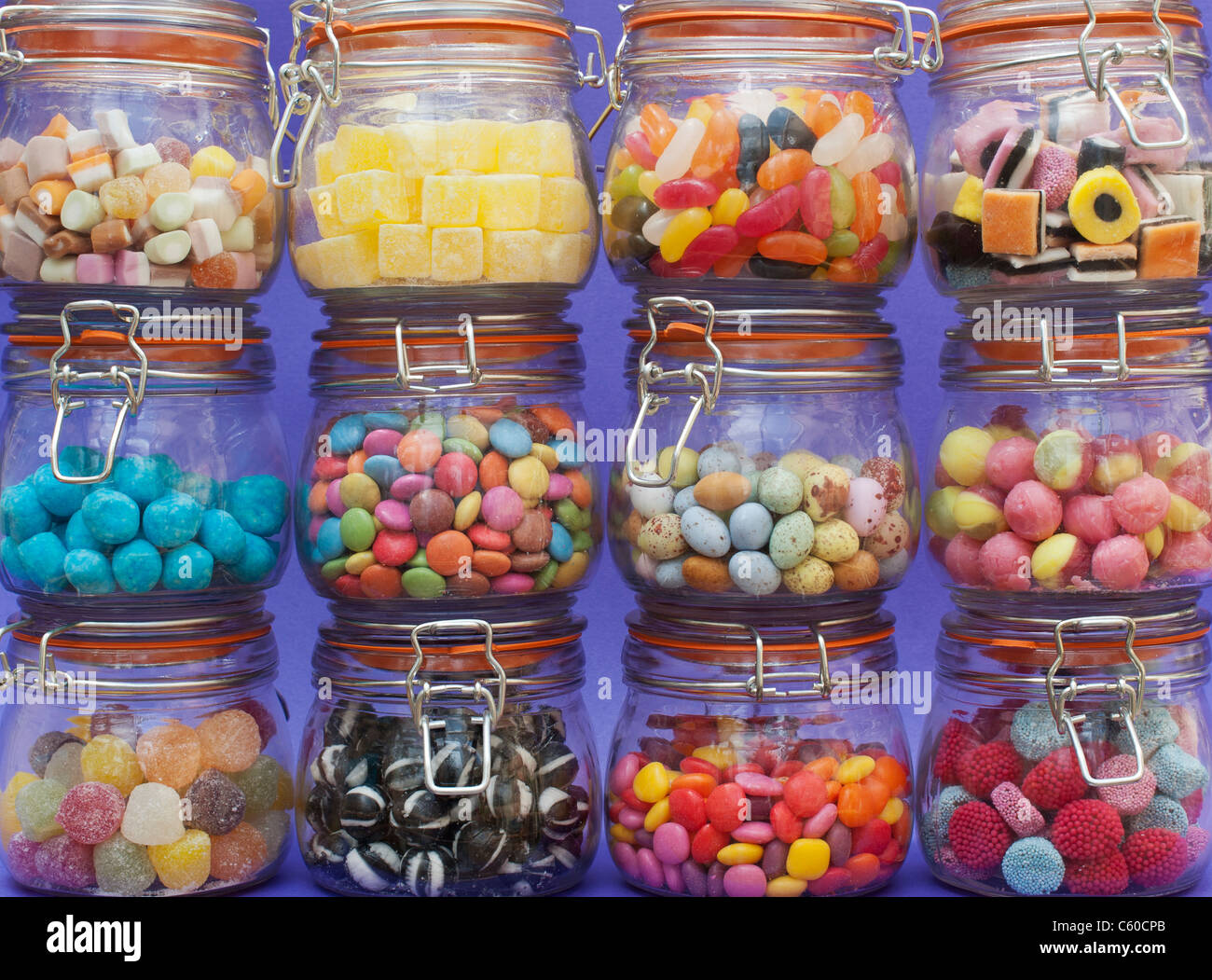 Colourful childrens sweets in kilner jars. Liquorice allsorts, Smarties, pineapple cubes, humbugs, bonbons, dolly - Stock Image