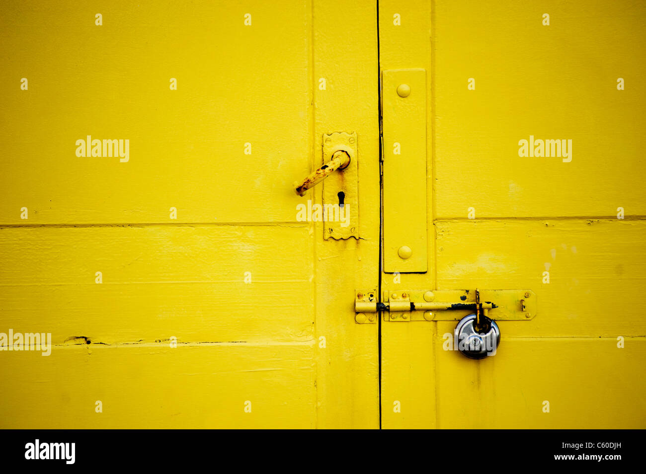 Bright yellow beach hut door close up - Stock Image
