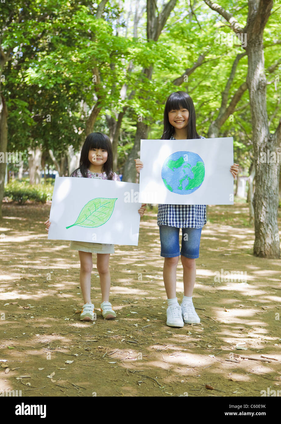 Sisters holding drawings of leaf and globe - Stock Image