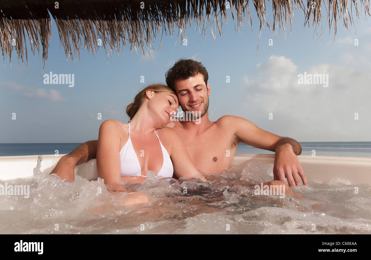 Couple embracing in hot tub - Stock Image