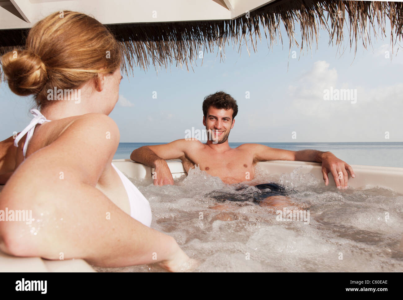 Couple sitting in hot tub - Stock Image