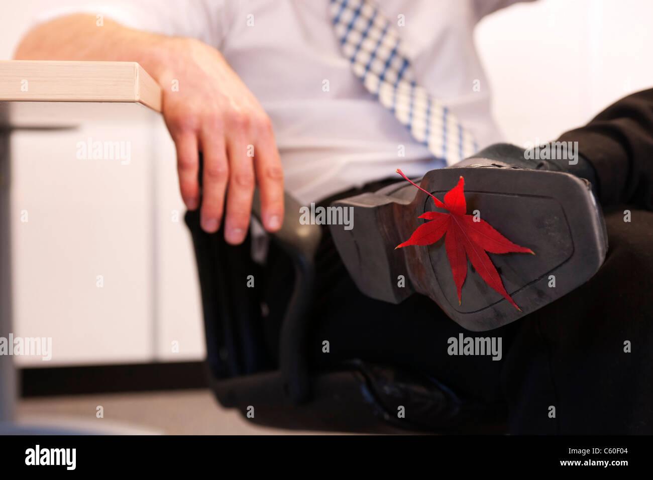 Leaf stuck to businessman's shoe - Stock Image