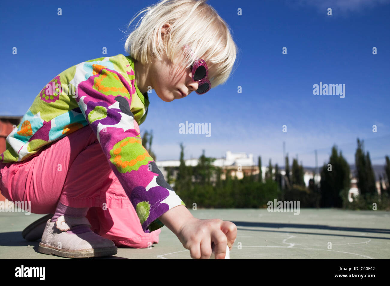 Girl drawing with sidewalk chalk - Stock Image