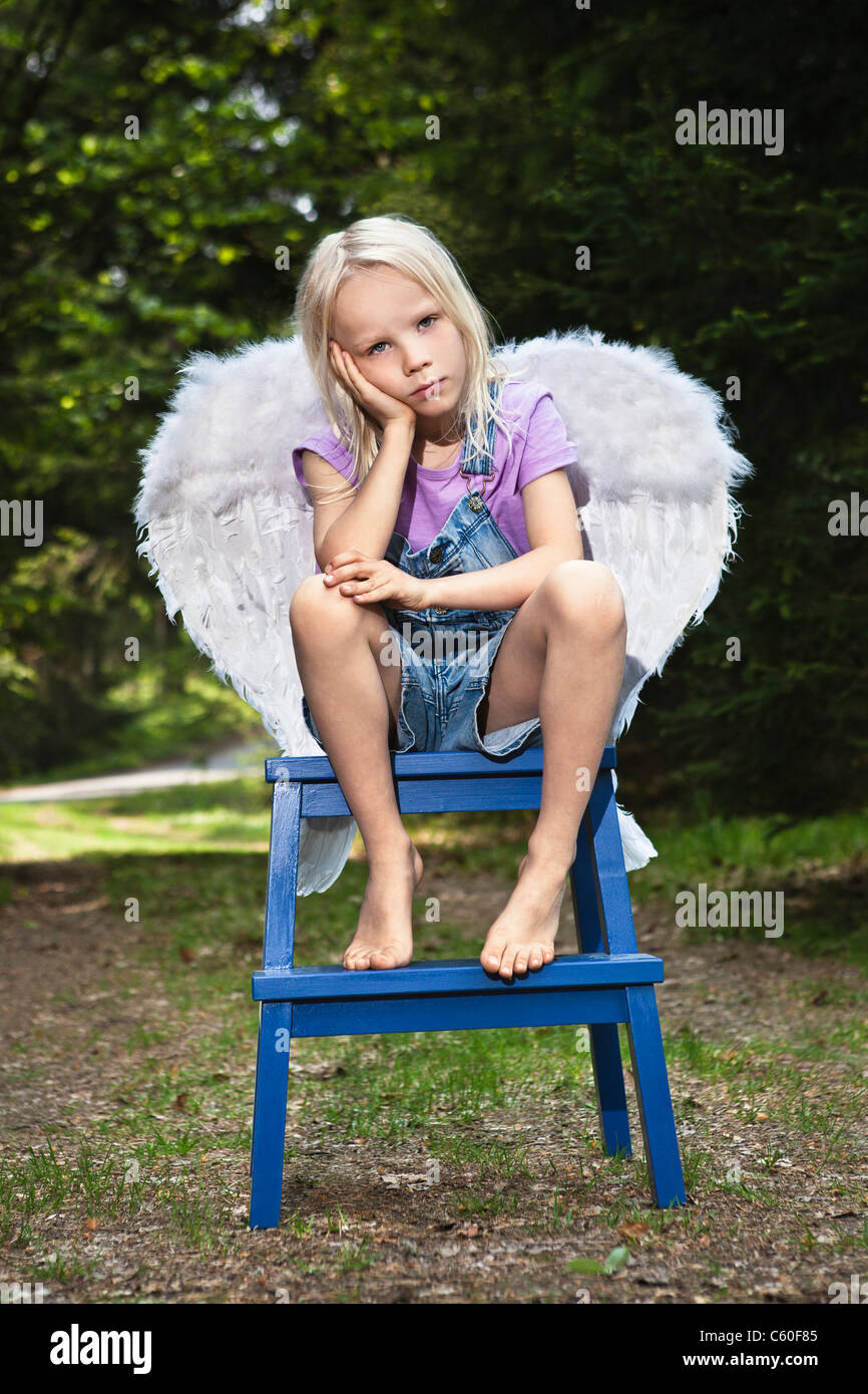 Bored girl in wings sitting on stool - Stock Image