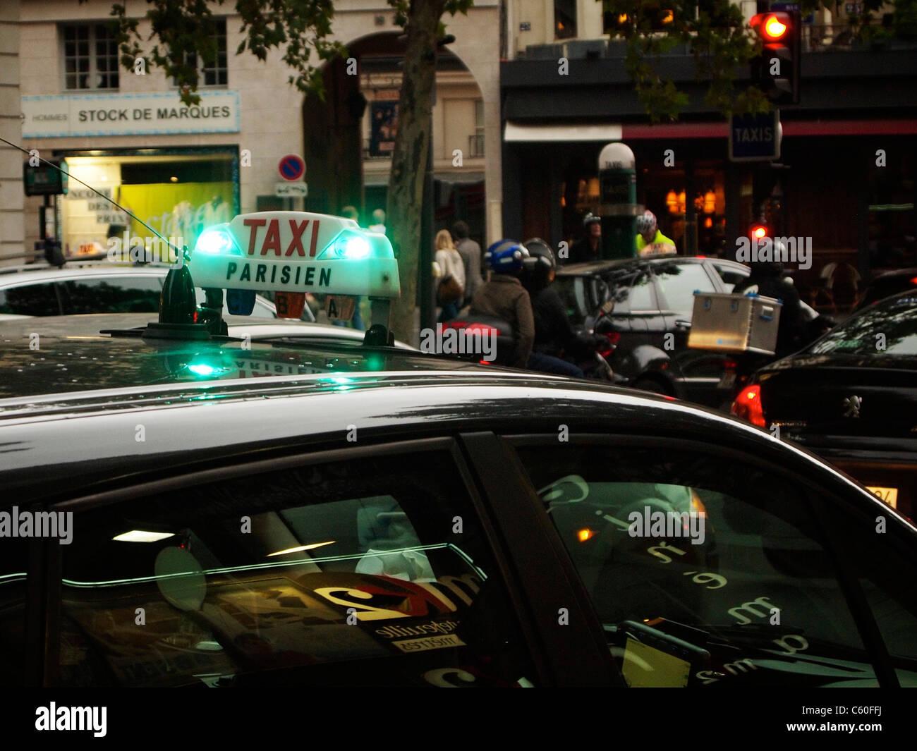 Illuminated Taxi Parisien sign in the evening, Paris Saint Germain quarter. - Stock Image