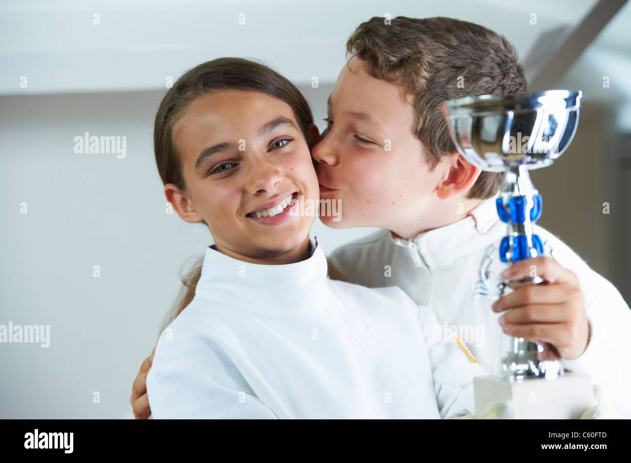 Boy kissing smiling fencing rival - Stock Image
