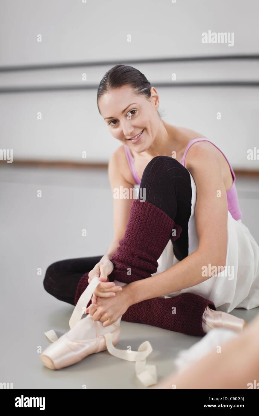 Ballet dancer tying her shoe in studio - Stock Image