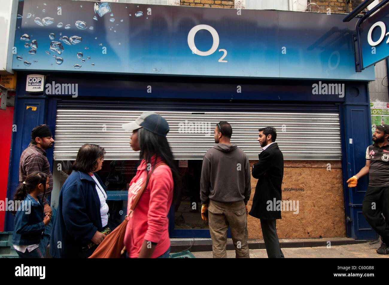 Hackney . The Narrow Way. O2 mobile phone shop attacked last night. Passers by in front of damaged window. - Stock Image