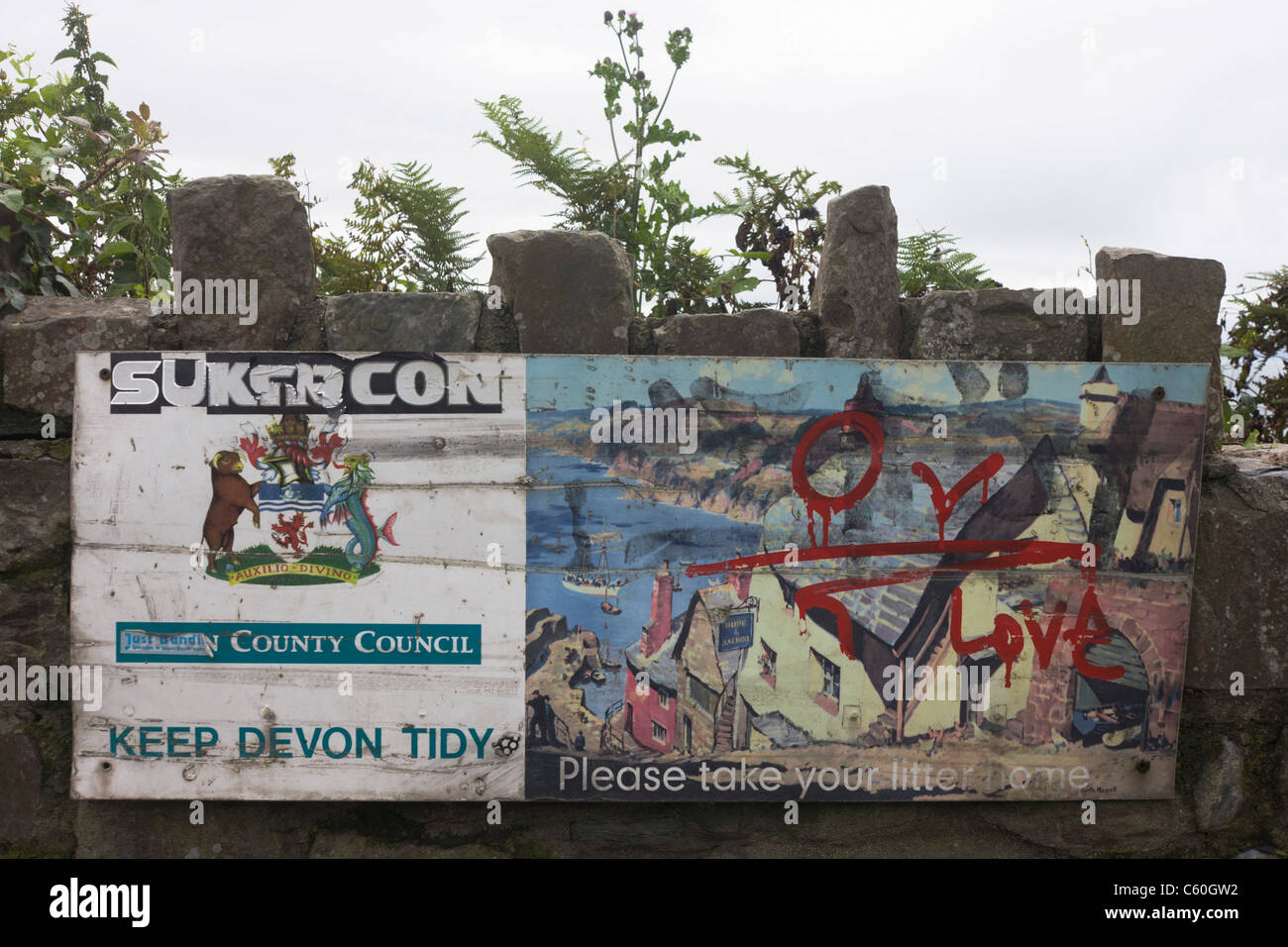 A dirty Keep Devon Tidy council sign discouraging litter at their seaside has been written over by graffiti. Stock Photo