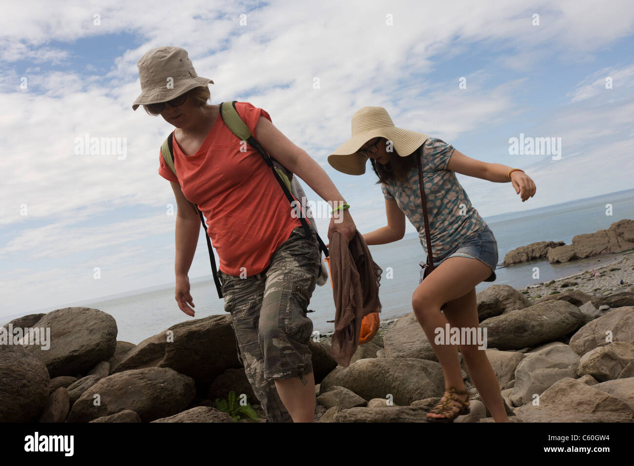 Mother and daughter tread over smooth rocks at Trentishoe Cove, north Devon. - Stock Image