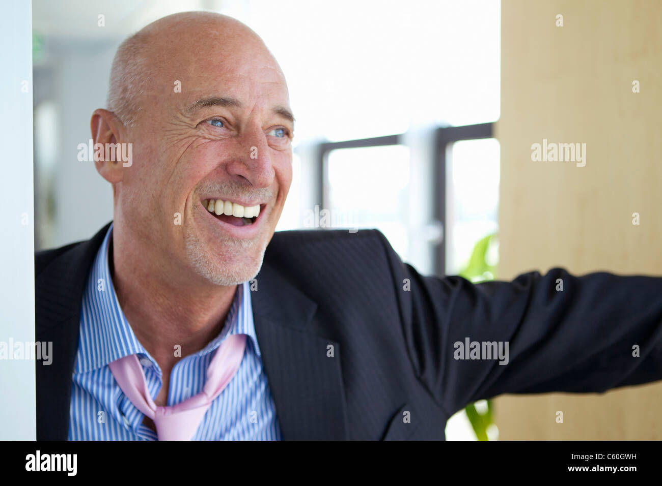 Laughing businessman in loose tie - Stock Image
