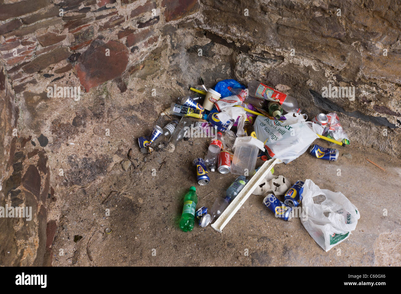 Beer cans and other rubbish collects in a corner of a heritage structure on the beach at Croyde, north Devon. Stock Photo