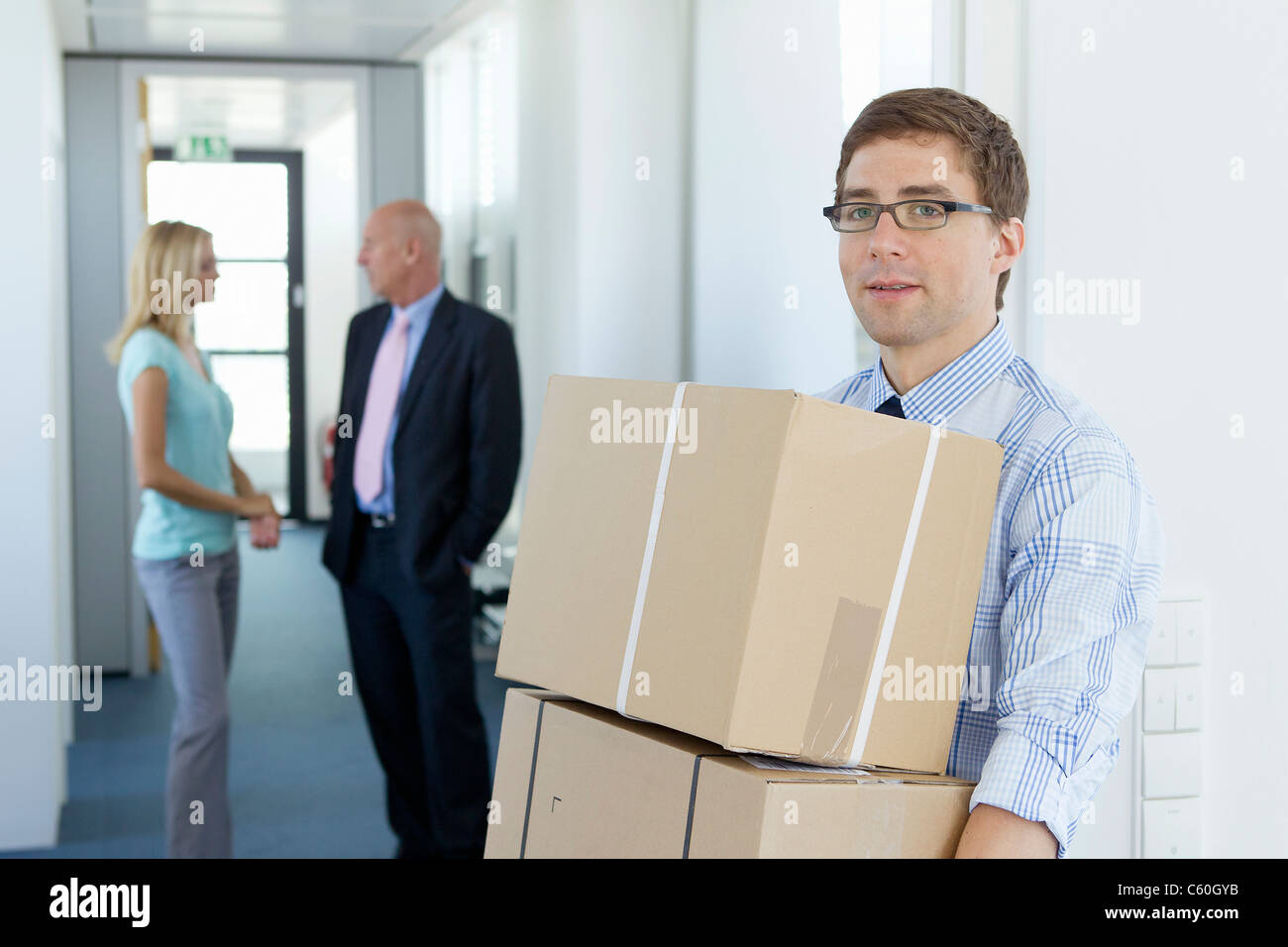 Businessman carrying cardboard boxes - Stock Image