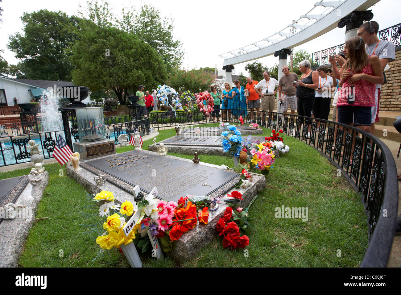 tourists visit elvis's grave in the meditation garden at graceland memphis tennessee usa - Stock Image