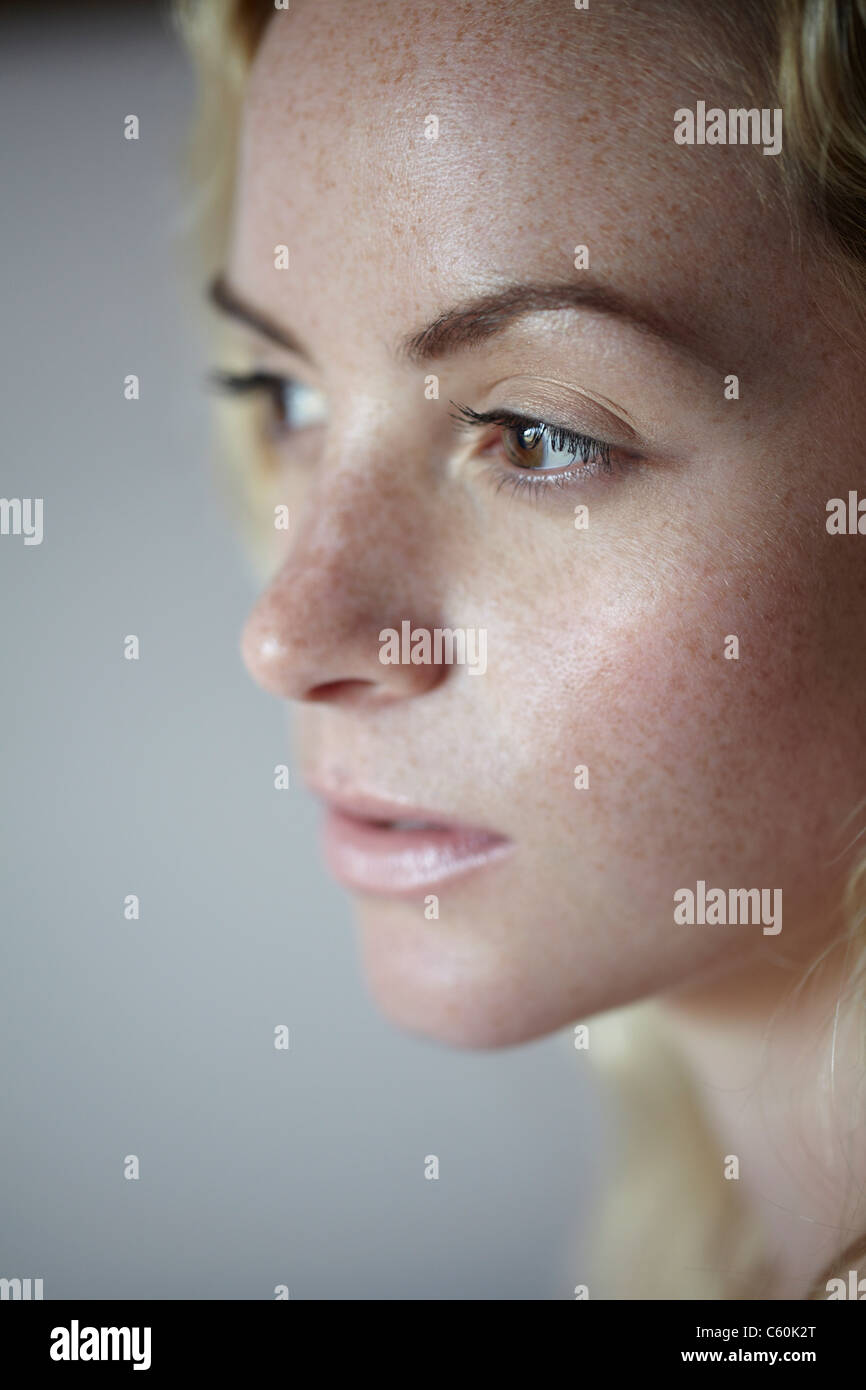 Close up of woman's freckled face - Stock Image
