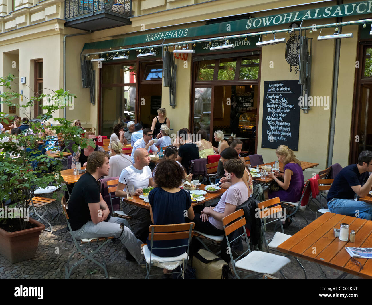 Busy pavement cafe serving brunch on a weekend morning in Prenzlauer Berg in Berlin Germany - Stock Image