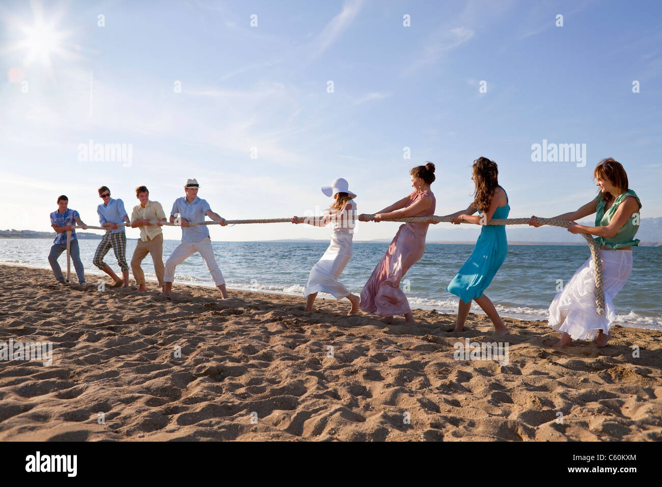 Newlyweds and guests playing tug of war - Stock Image