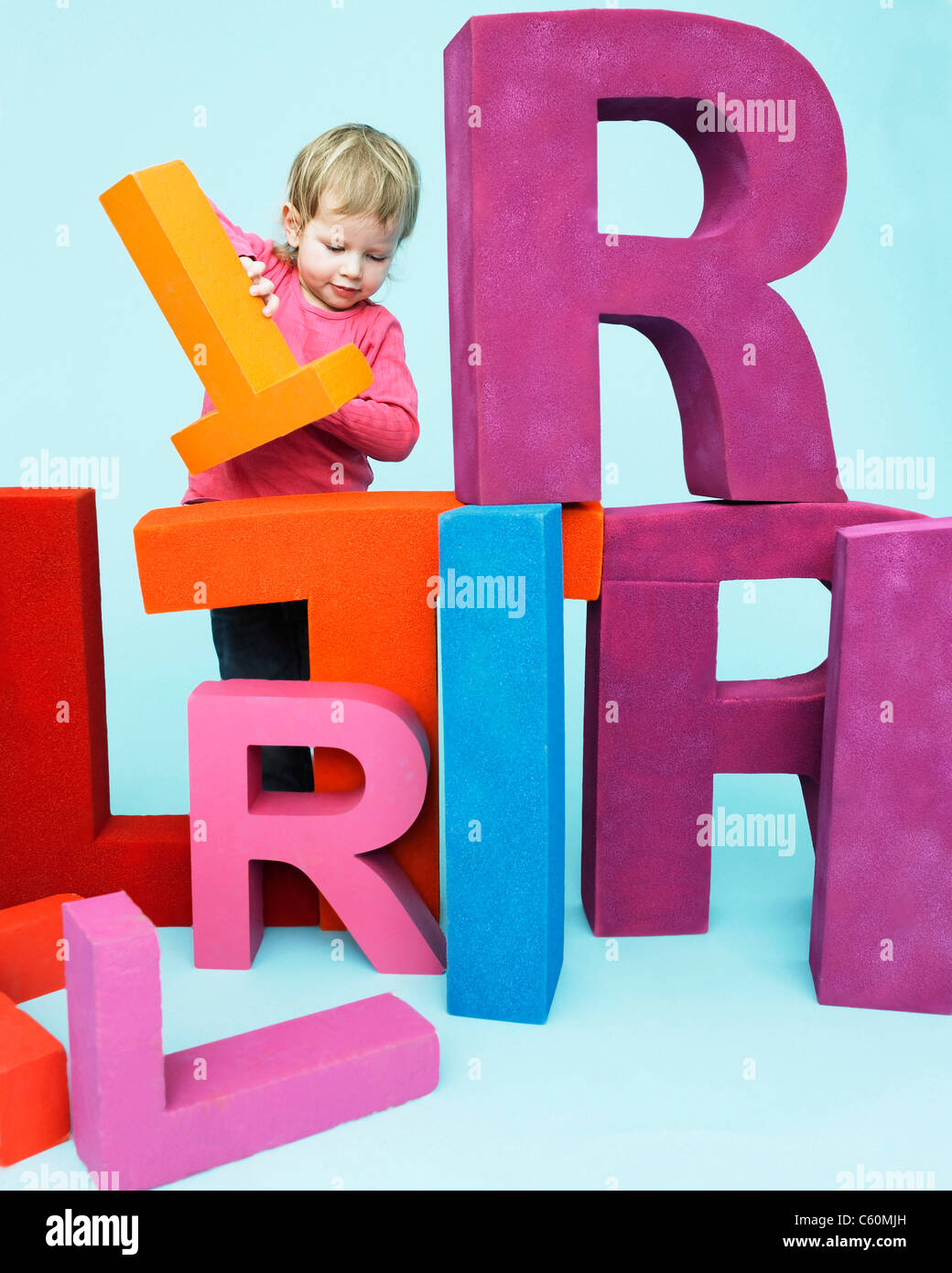 Toddler playing with oversize letters - Stock Image