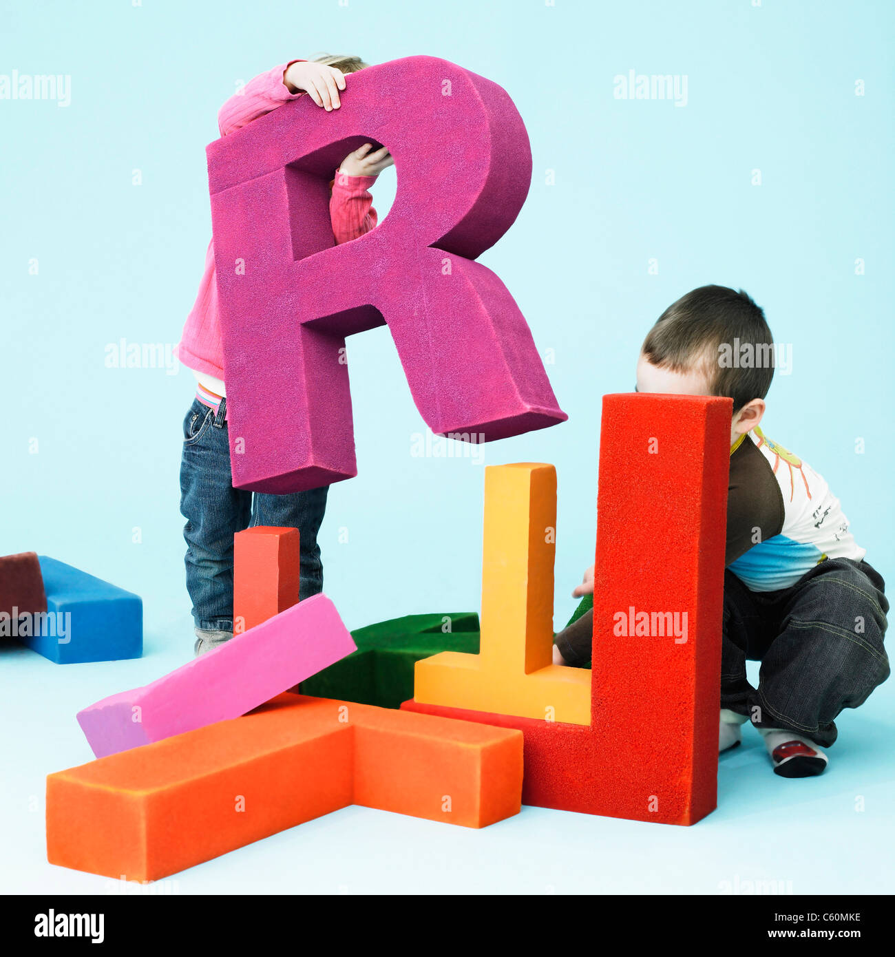Toddlers playing with oversize letters - Stock Image