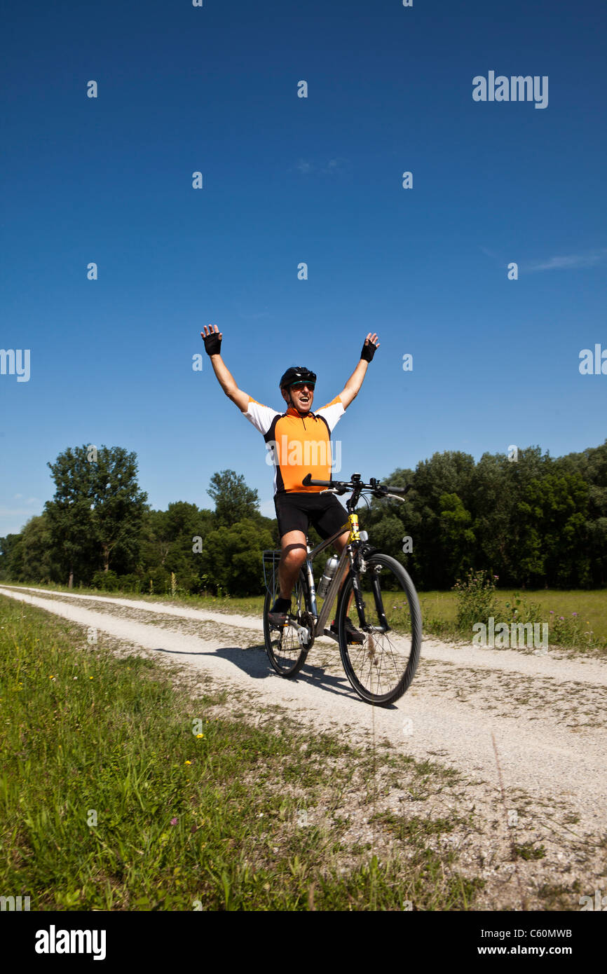 Biker cheering on dirt road - Stock Image