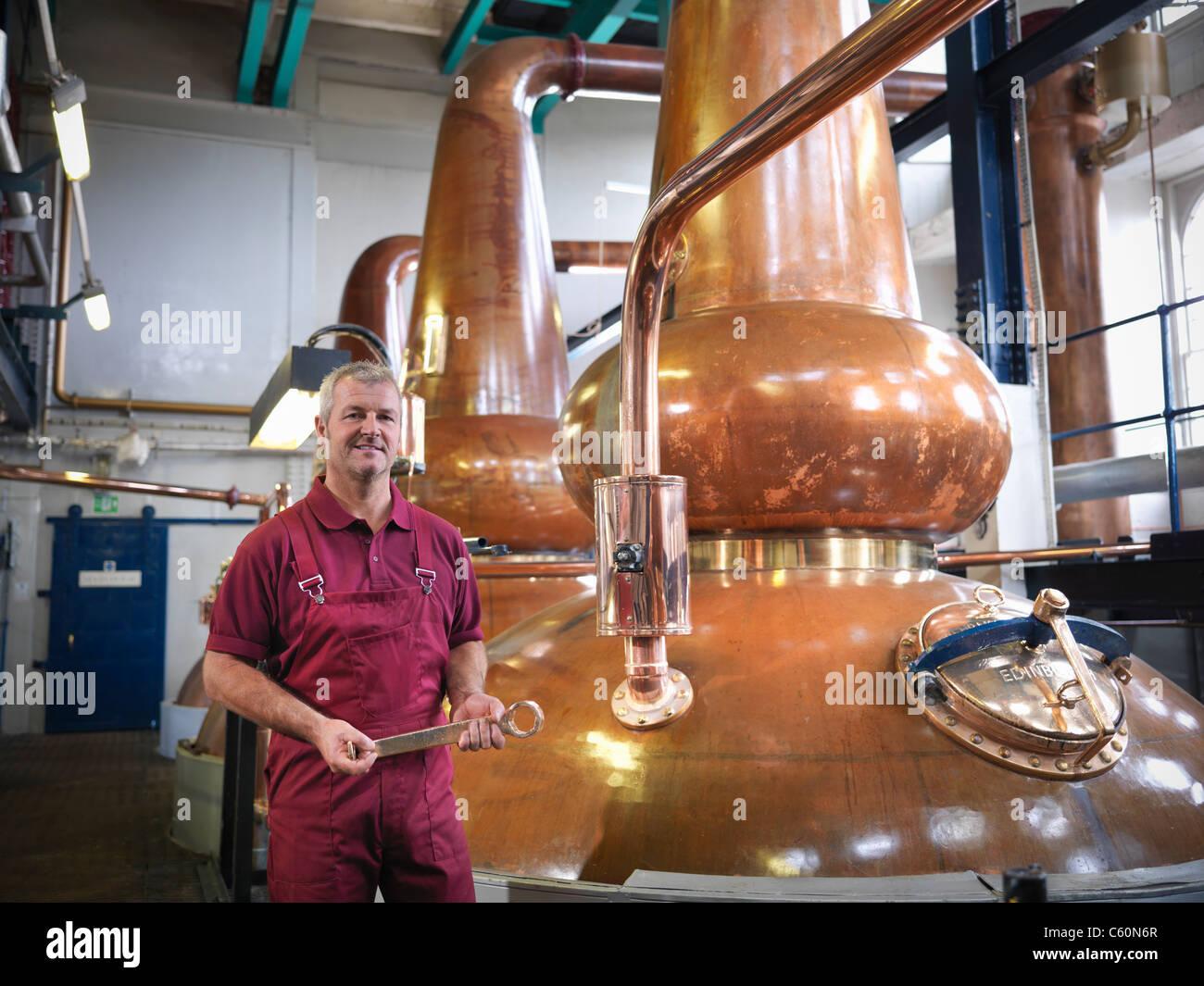 Worker with stills in distillery - Stock Image