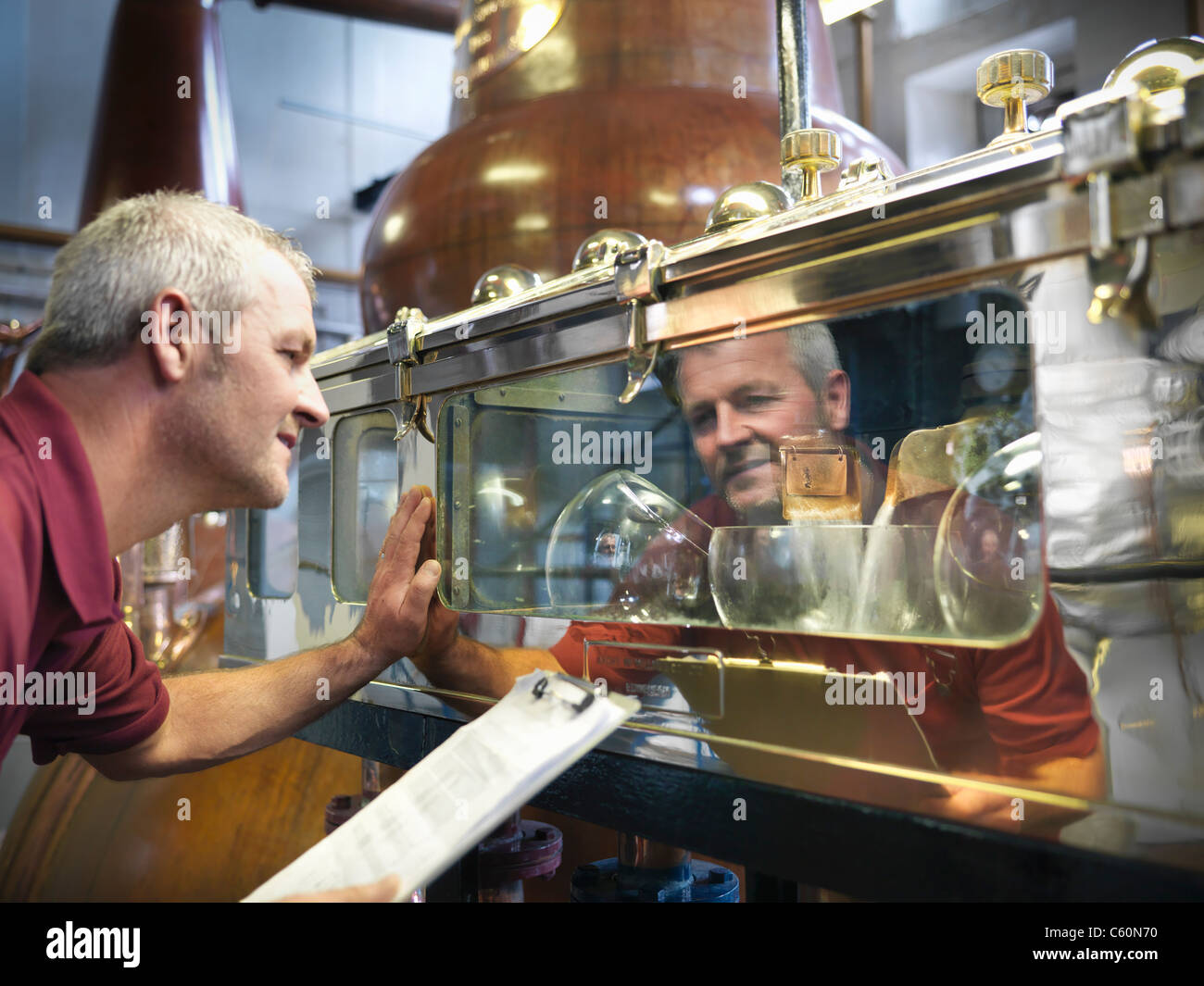 Worker checking whisky in distillery - Stock Image