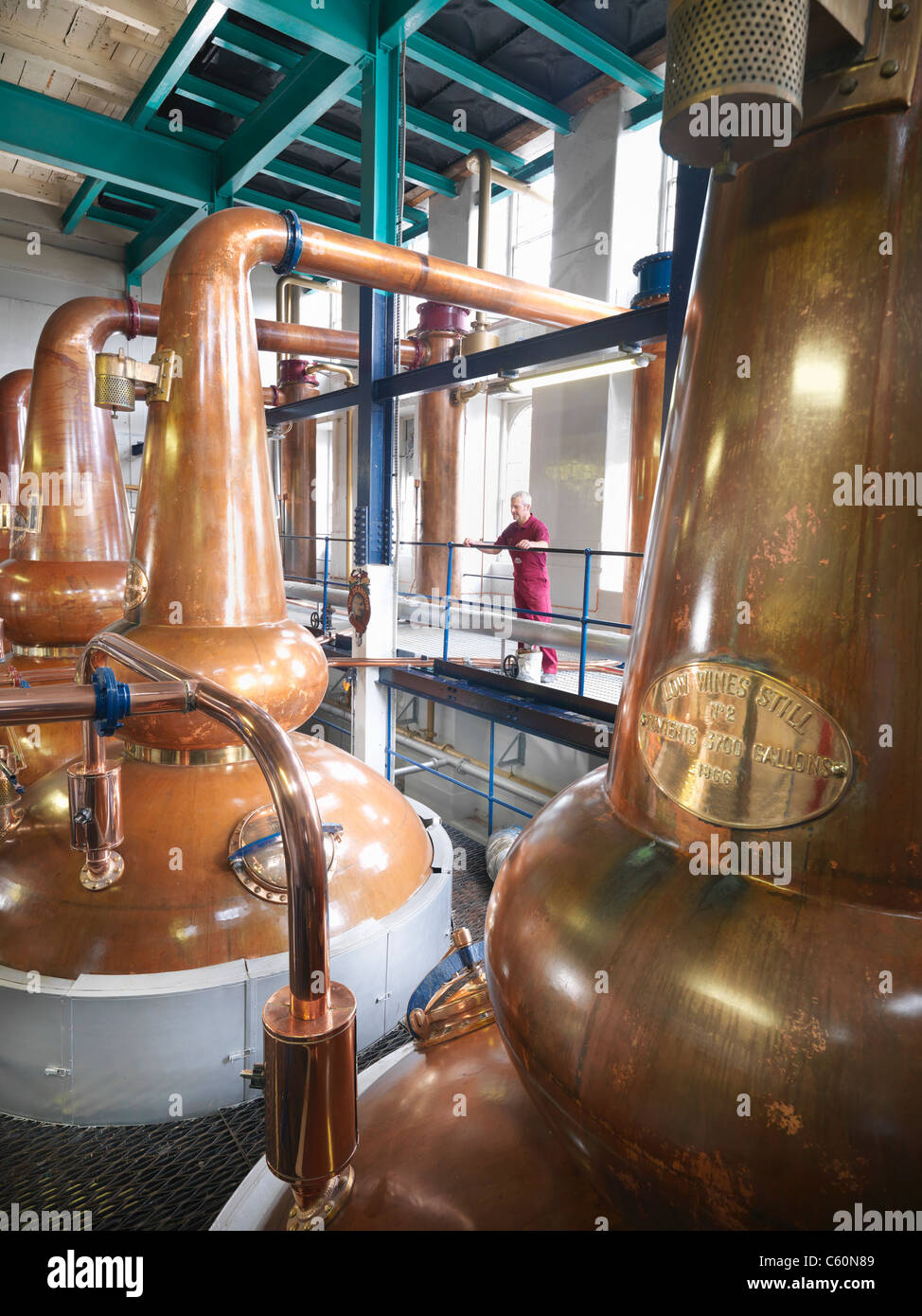 Worker checking stills in distillery - Stock Image