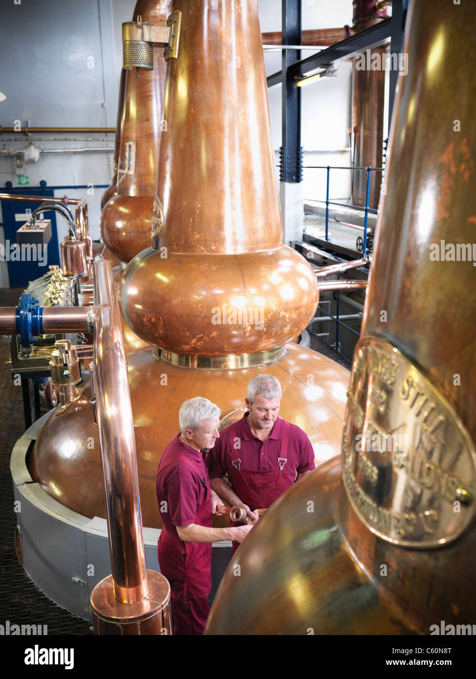 Workers checking stills in distillery - Stock Image