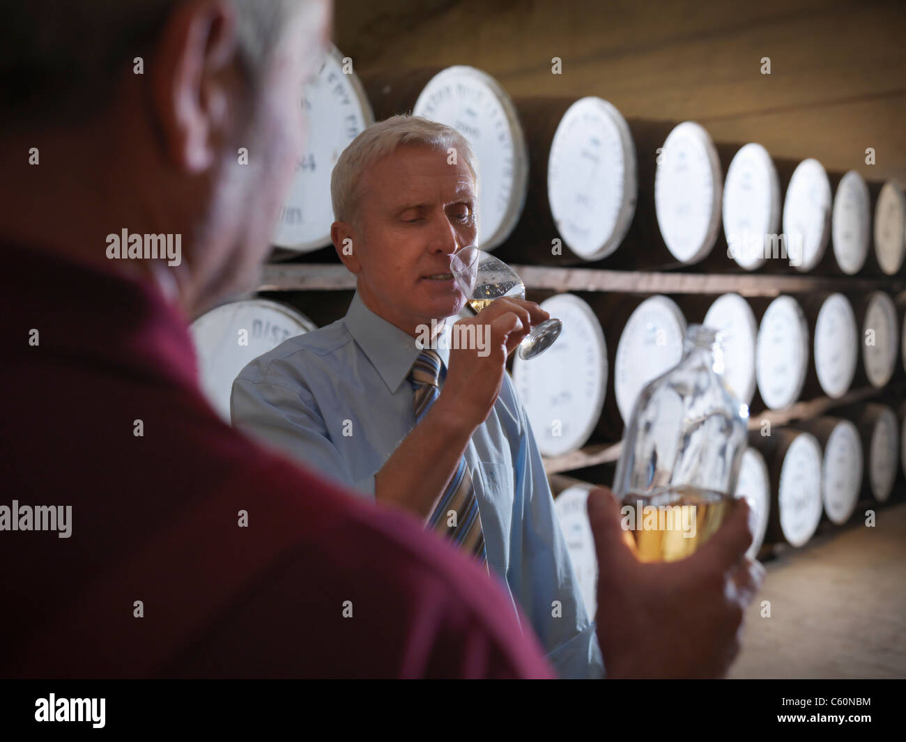Workers checking whisky in distillery - Stock Image