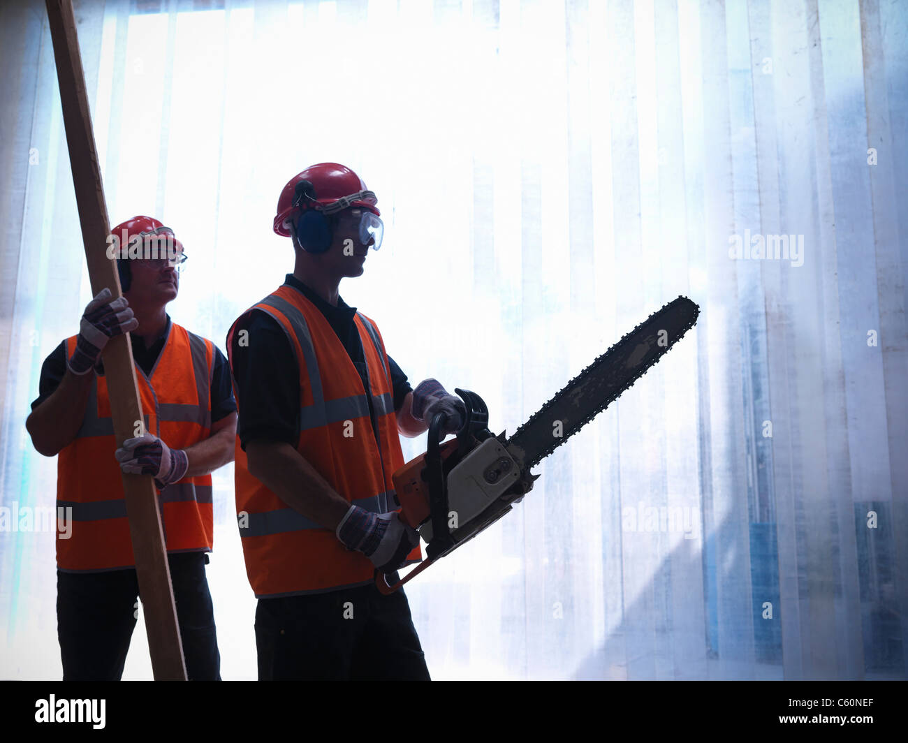 Workers with chainsaw and wooden plank - Stock Image