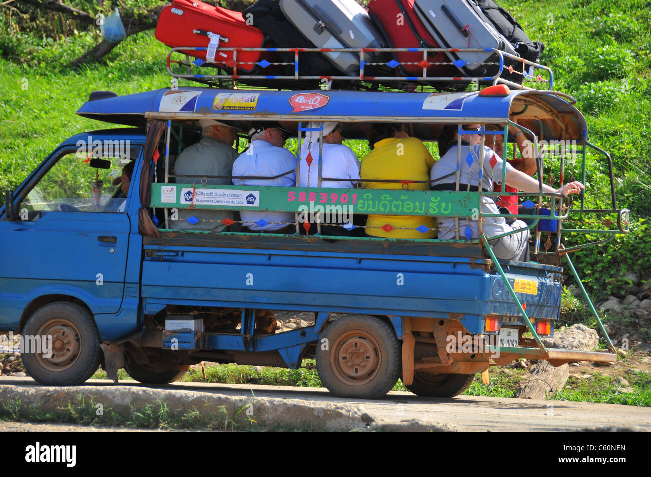 tourists packed in tightly in a taxi car  in Laos ASIA - Stock Image