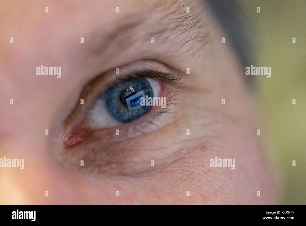 Close-up of a man's blue left eye with facebook reflected in it - Stock Image