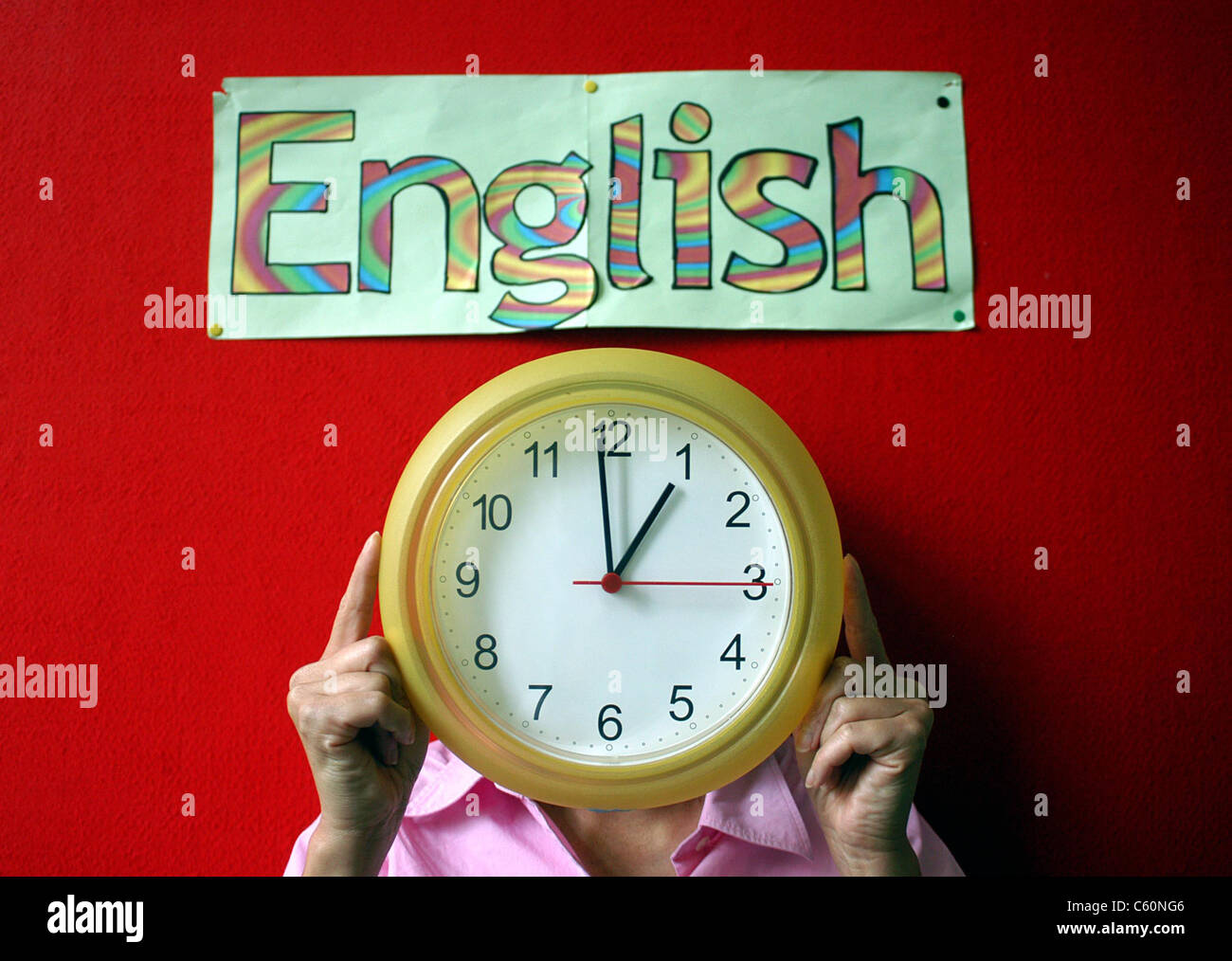 Adult holding up a yellow clock, stood against a red wall with an artwork poster saying English, in multi-coloured - Stock Image