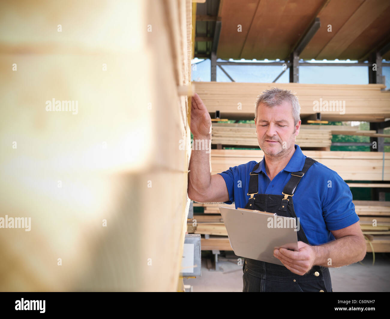 Worker checking wooden planks in joinery - Stock Image