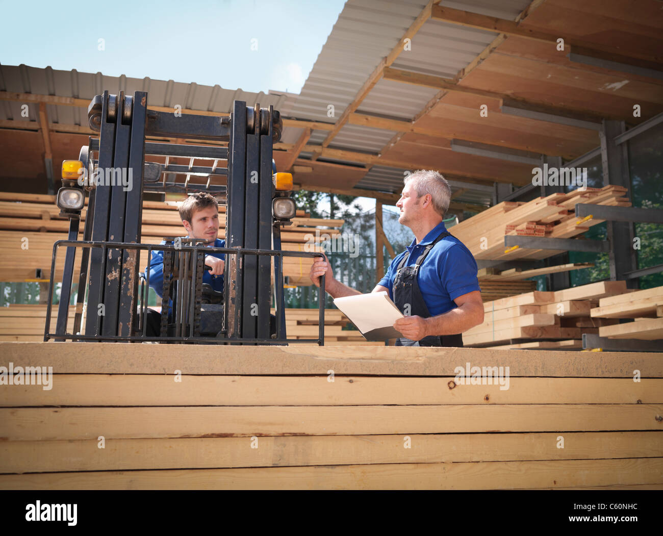 Worker carrying planks on forklift - Stock Image